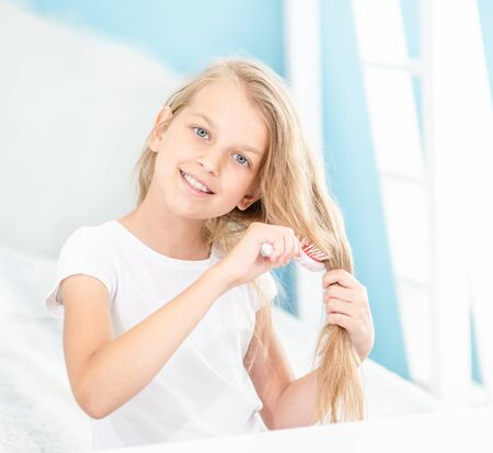 Happy little girl combing hair in the morning at home.