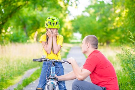 Father calms his sad daughter who did not get to ride a bike.