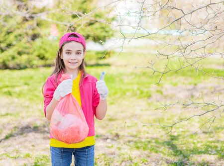 Girl with a bag of trash in a summer park showing thumbs up. Volunteer and ecology concept. Empty space for text.