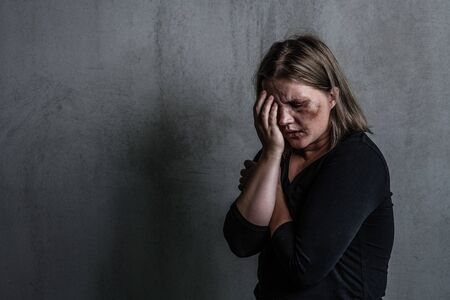 Crying woman victim of domestic violence and abuse. Empty space for text.