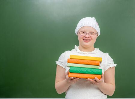 Smiling girl with Down Syndrome stands near a school board with books. Empty space for text. Archivio Fotografico