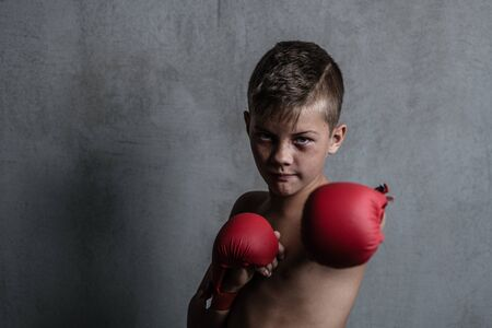 Beaten young boy punching with red boxing gloves. Empty space for text. Archivio Fotografico