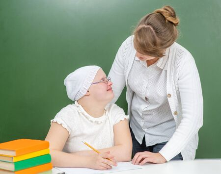 Teacher helps young girl with Down Syndrome at school. Фото со стока