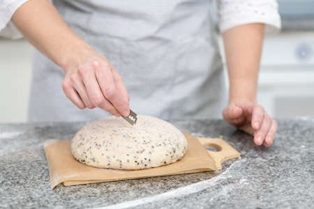 Baker making patterns on raw bread using a knife ot blade to shape the dough prior to baking. Manufacturing process of a bread at home.