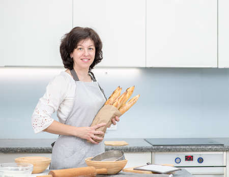 Young woman holds a grocery bag full of bread at home.
