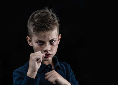 Beaten young boy is ready to fight. Empty space for text. Isolated on dark background.