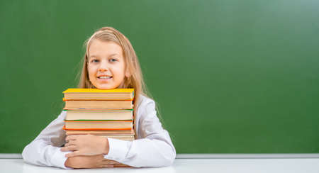 Smiling young girl sits with books near empty green chalkboard. Empty space for text.