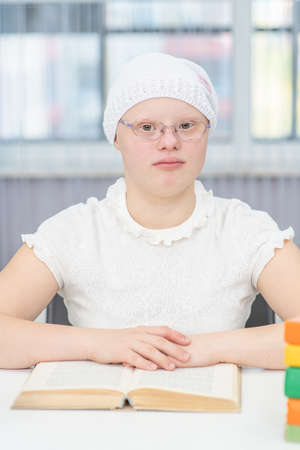 Portrait of a smart girl with Down Syndrome with books at home. Imagens - 154370555