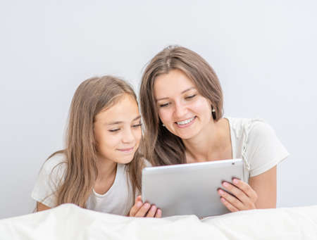 Happy family at home. Beautiful young woman and her little daughter are using a digital tablet and smiling while lying in bed at home.