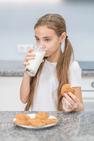Young girl drinks milk with cookies at kitchen.