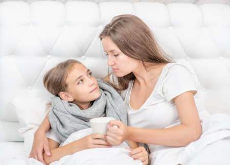 Mother taking care of sick daughter in the bedroom and giving her cup of the tea. Imagens - 154370562