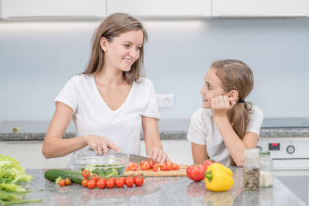 Happy mom and her daughter cook dinner in the kitchen.