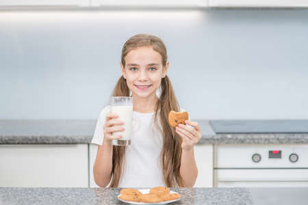 Smiling girl holds cookies and glass of the milk at kitchen. Imagens - 154370565