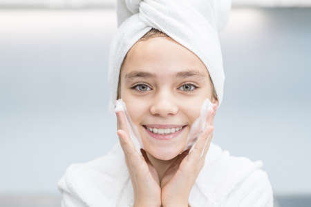 Smiling young girl washes her face in bathroom at home.