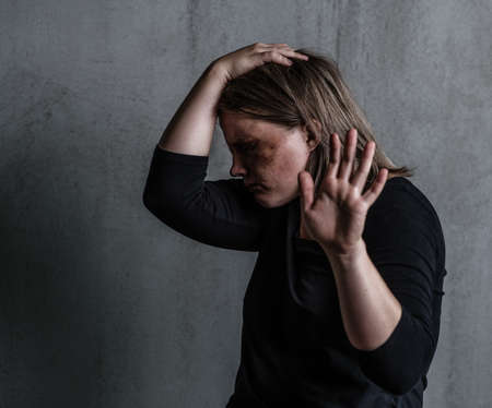 Crying woman victim of domestic violence and abuse showing a stop sign and closes her head with her hand.