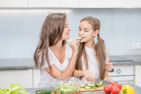 Happy mother and young girl preparing healthy food and having fun at home. Imagens