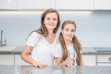 Smiling woman hugs her daughter who holds a glass of water at the kitchen.