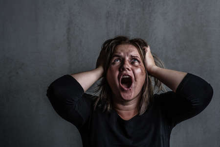 Angry young woman victim of domestic violence and abuse having nervous breakdown screaming.