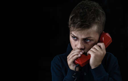 Young boy victim of domestic violence and abuse asks for help by phone. Empty space for text. Imagens