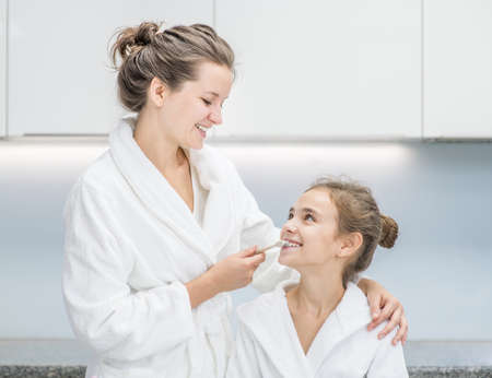 Happy family at home. Smiling mom teaching her young daughter how to brush teeth with toothbrush. Imagens