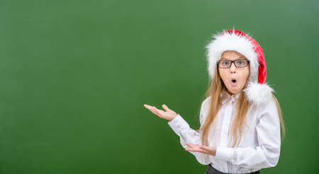 shocked girl wearing a red christmas hat and eyeglasses points away on empty chalkboard. Space for text. Imagens - 155155481