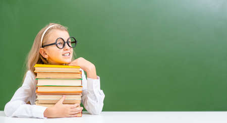 Young girl wearing a eyeglasses sits with bokks and looks away at the empty space of the chalkboard. Empty space for text.