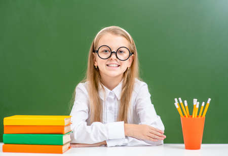 Smiling young girl wearing a eyeglasses sits with books near empty green chalkboard. Imagens - 155155225