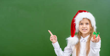Smiling girl wearing a red christmas hat holds gift box and points away on empty chalkboard. Space for text.