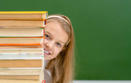 Smiling girl looks from behind a stack of books near empty green chalkboard. Empty space for text.