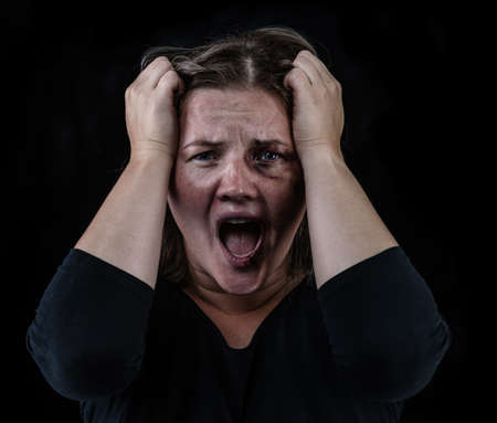 Angry young woman victim of domestic violence and abuse having nervous breakdown screaming. Isolated on black background.