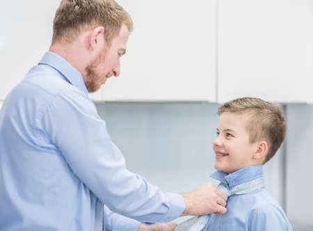 Dad helps son tie a tie at home.