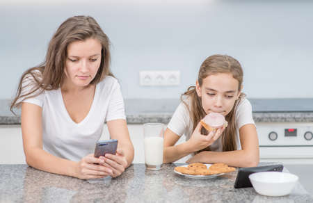 Young woman and her daughter use smartphones while having dinner at kitchen.