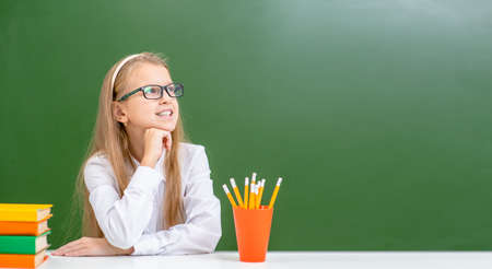 Young female student wearing a eyeglasses looks away at the empty space of the chalkboard. Empty space for text. Imagens