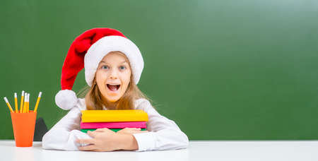 Shocked girl wearing a red christmas hat sits near green chalkboard. Empty space for text.