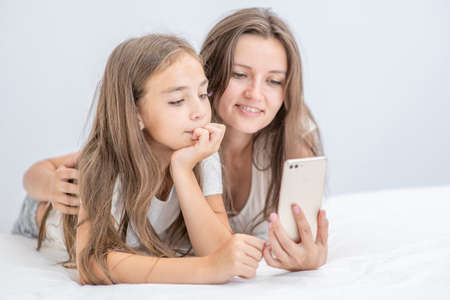 Happy family at home. Beautiful young woman and her little daughter are using a smartphone and smiling while lying in bed at home.