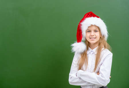 Smiling girl wearing a red christmas hat stands near green chalkboard. Empty space for text.