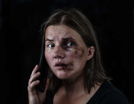 Woman victim of domestic violence and abuse asks for help by phone. Isolated on dark background.