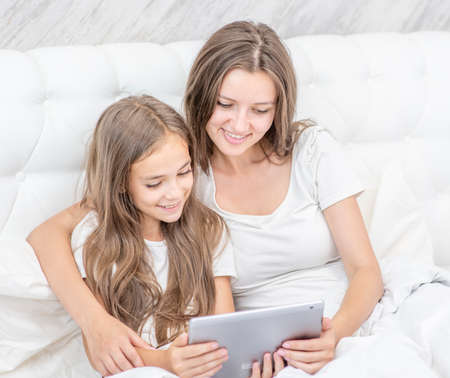 Beautiful young woman and her little daughter are using a digital tablet and smiling while sitting on the bed at home.