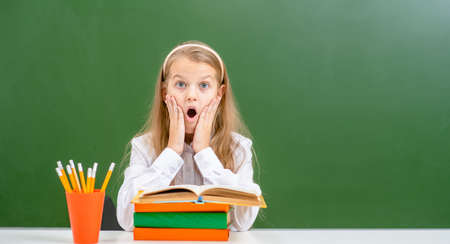 Surprised girl sits near empty chalk board with books. Empty space for text.