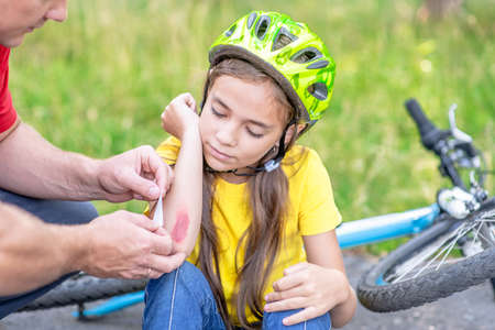 Dad puts a bandage on a wound to little girl, who fell off his bicycle.