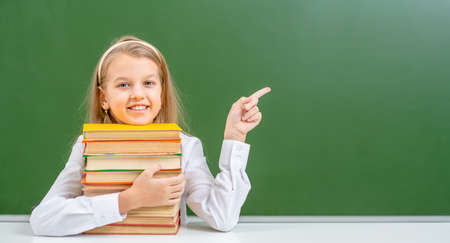 Young girl hugs with books and points away on empty green chalkboard. Empty space for text.