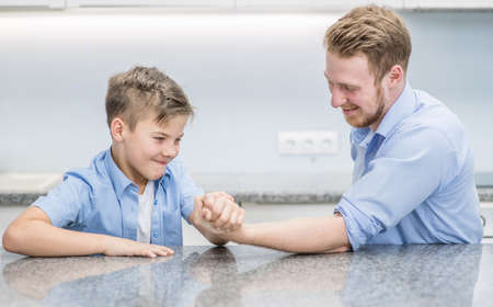 Young boy wins his father in arm wrestling.