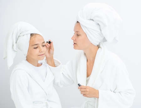Mother and young daughter applying makeup at home. Mom and child girl are in bathrobes and with towels on their heads.