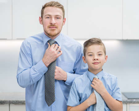 Happy boy and his father tying neckties at home. Imagens - 155155381