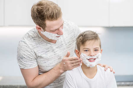 Father applying shaving foam on face his young son.