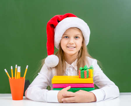 Portrait of a smiling girl wearing a red christmas hat sits with books near green chalkboard.