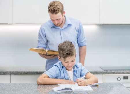 Father helps son do schoolwork at home.