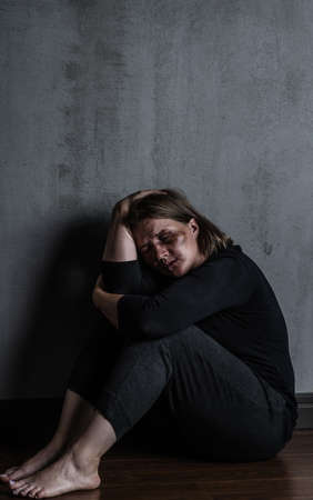 Sad woman victim of domestic violence and abuse sits on a floor at home. Empty space for text.