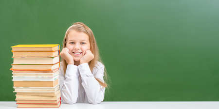 Smiling young girl sits with books near empty green chalkboard. Empty space for text. Imagens
