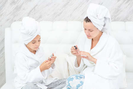 Mother and her daughter are doing manicures at home. Mom and child girl are in bathrobes and with towels on their heads. Imagens